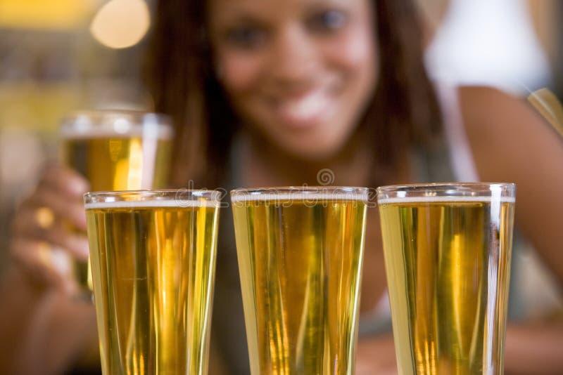 Een jonge vrouw met drie bieren in rij stock foto's