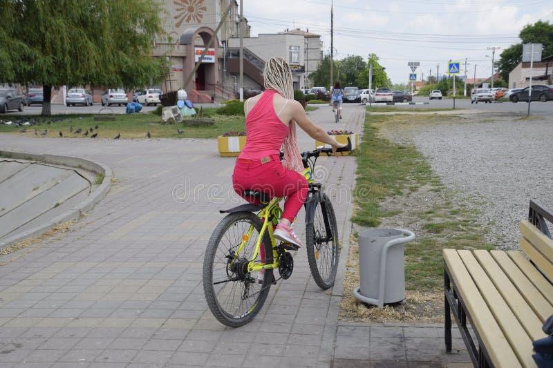 Een jonge vrouw met een gele bergfiets berijdt langs de stoep Een gang op een fiets in het park Meisje met stock foto