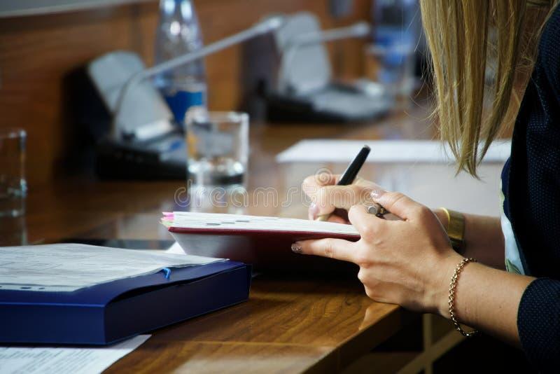 Een jonge vrouw met een gouden armband schrijft nota's in een dik notitieboekje Verslag in de organisator stock afbeelding