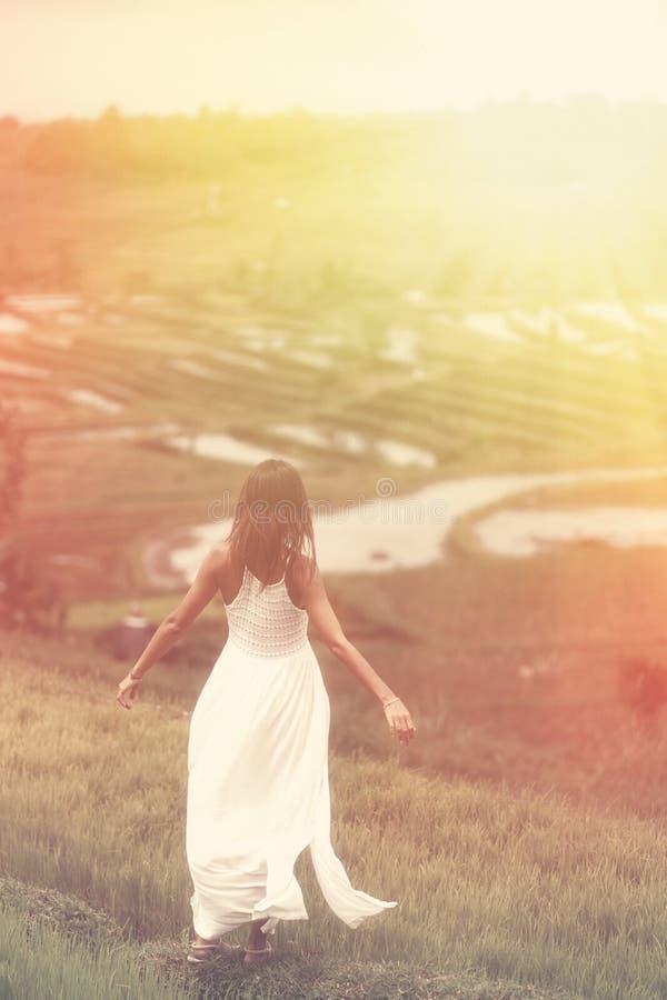 Een jonge vrouw met haar wapens het uitgestrekte stellen die zich op een heuvel bevinden Op de achtergrond zijn padievelden r stock foto's