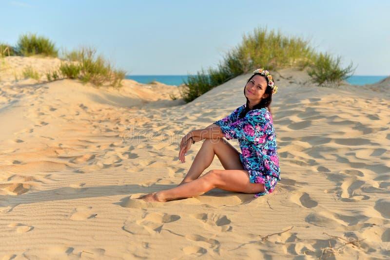 Een jonge vrouw met een kroon van bloemen op haar hoofd die op een zandig strand rusten royalty-vrije stock afbeeldingen