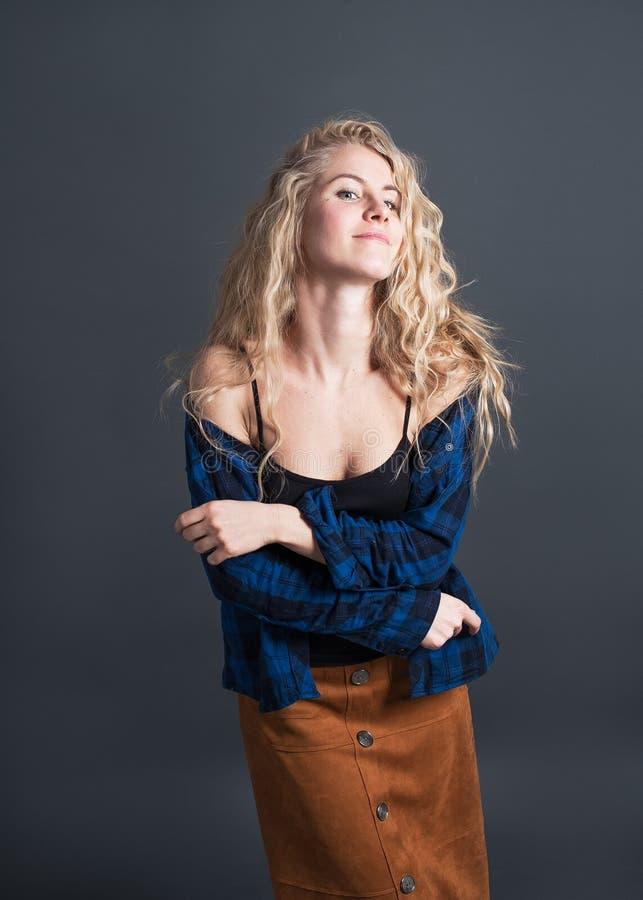 Een jonge vrouw met lang blond golvend haar danst tegen een donkere achtergrond Positieve geïsoleerde emoties, gelukkig, hipster  stock afbeeldingen