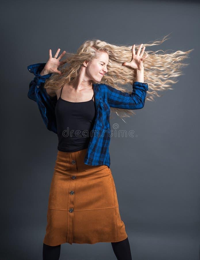 Een jonge vrouw met lang blond golvend haar danst tegen een donkere achtergrond Positieve gelukkige emoties, hipster stijl, stock afbeelding