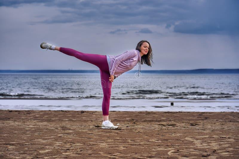 Een jonge vrouw met lang zwart haar is bezig geweest met gymnastiek op de zandige kust van een grote rivier royalty-vrije stock fotografie