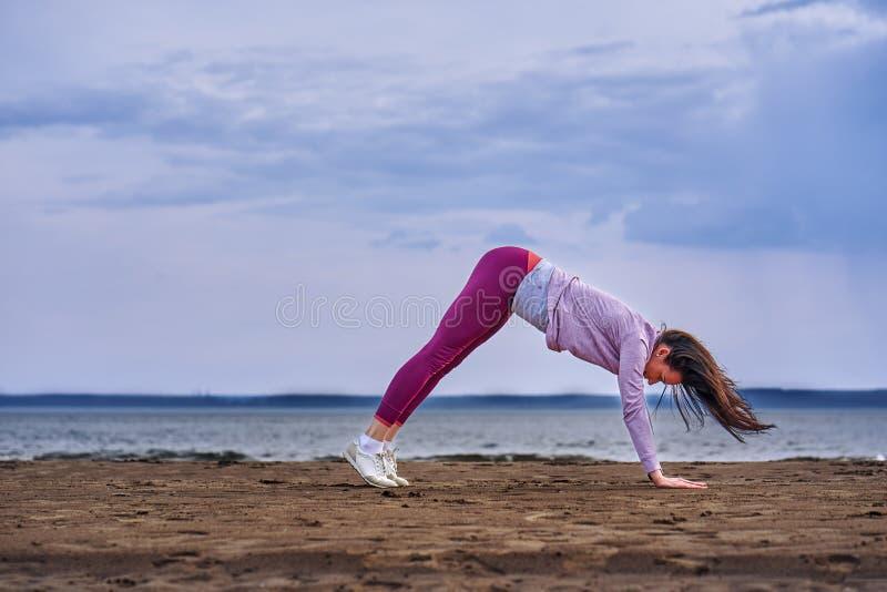 Een jonge vrouw met lang zwart haar is bezig geweest met gymnastiek op de zandige kust van een grote rivier royalty-vrije stock afbeelding
