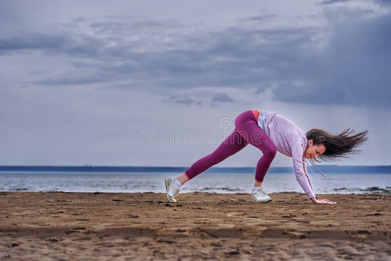 Een jonge vrouw met lang zwart haar is bezig geweest met gymnastiek op de zandige kust van een grote rivier stock foto's