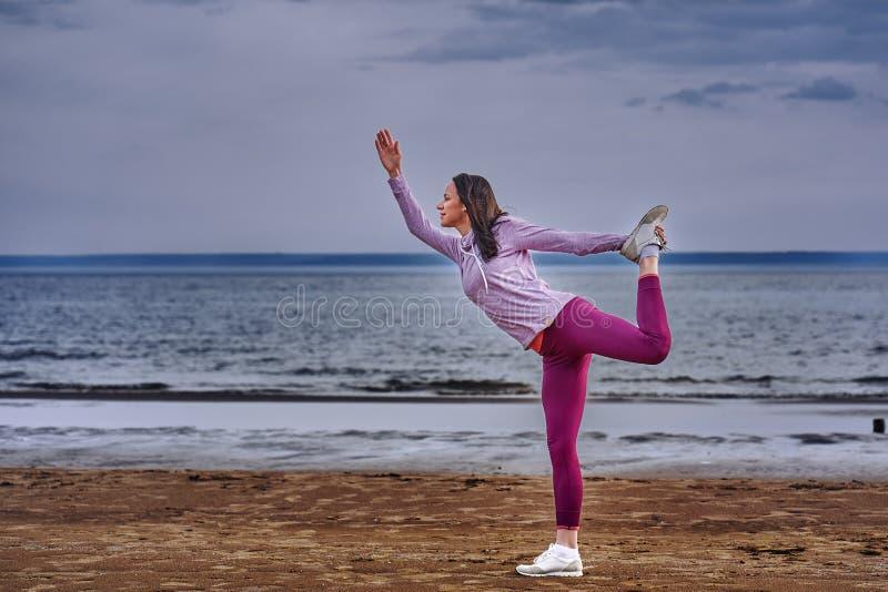 Een jonge vrouw met lang zwart haar is bezig geweest met gymnastiek op de zandige kust van een grote rivier royalty-vrije stock foto's