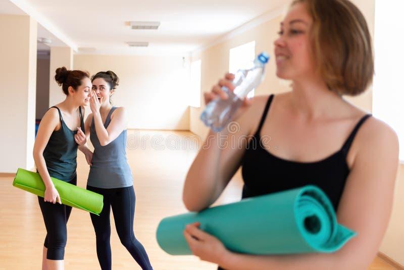 Een jonge vrouw met een Mat in haar handen drinkwater van een fles In de achtergrondtribunes twee vrouwen die aan elkaar fluister stock afbeeldingen