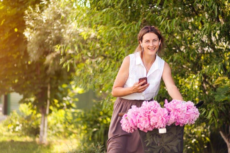 Een jonge vrouw met pioenen stock foto