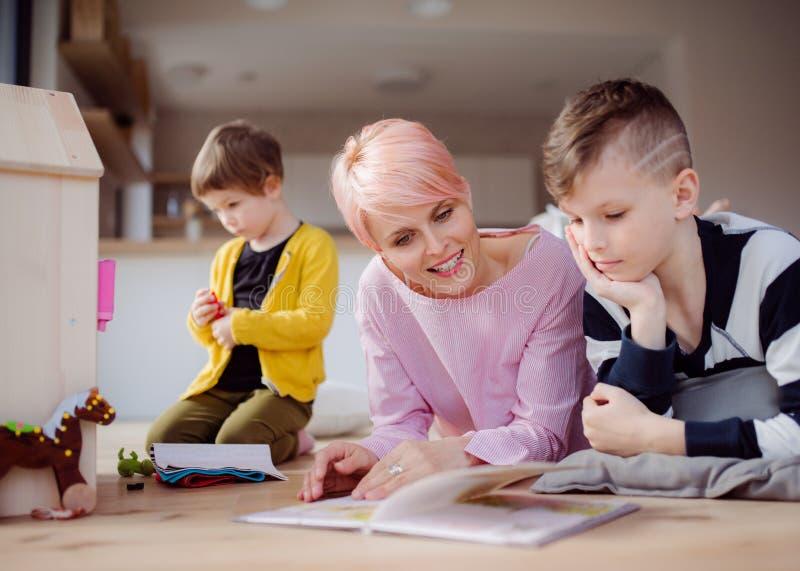 Een jonge vrouw met twee kinderen het lezen boekt en het spelen op de vloer stock afbeelding