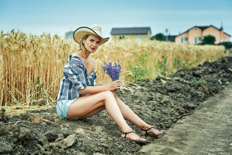 Een jonge vrouw op een gang op het gebied met tarwe stock foto