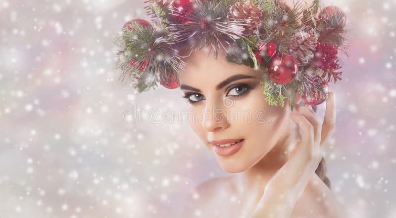 Een jonge vrouw, op haar hoofd een mooie kroon van sparren met kegels en ballen royalty-vrije stock afbeelding