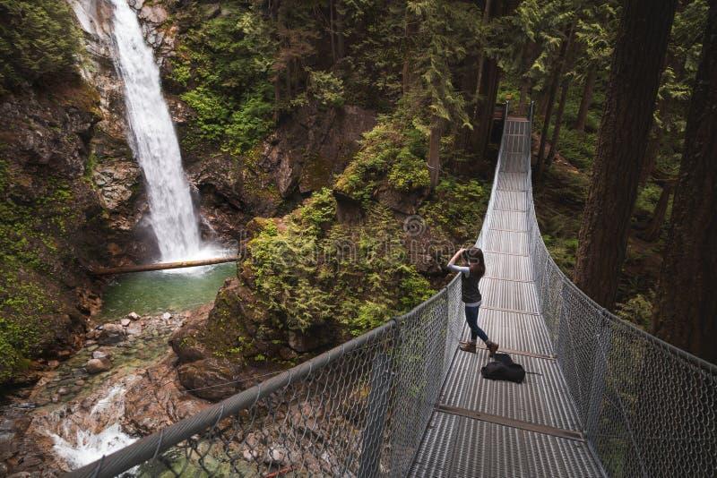 Een jonge vrouw op een hangbrug die een foto van een waterval nemen royalty-vrije stock afbeeldingen