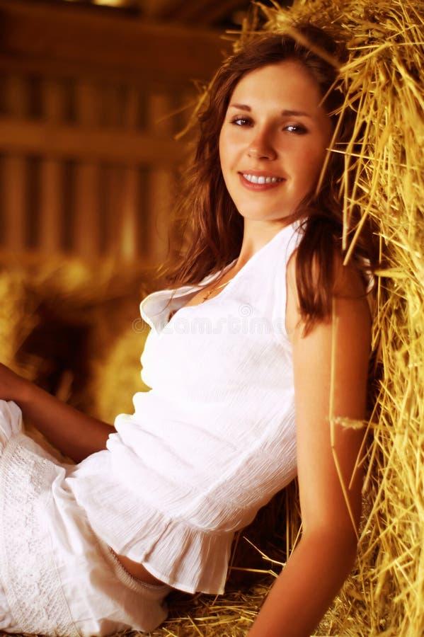 Een jonge vrouw rust op het hooi stock foto's