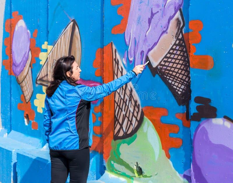 Een jonge vrouw schildert een beeld met een penseel op een concrete veiligheidsomheining op de grens tussen Israël en Libanon stock afbeeldingen