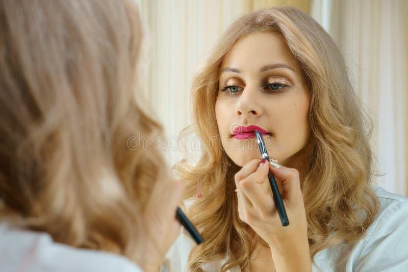 Een jonge vrouw schildert haar lippen bij de spiegel stock foto