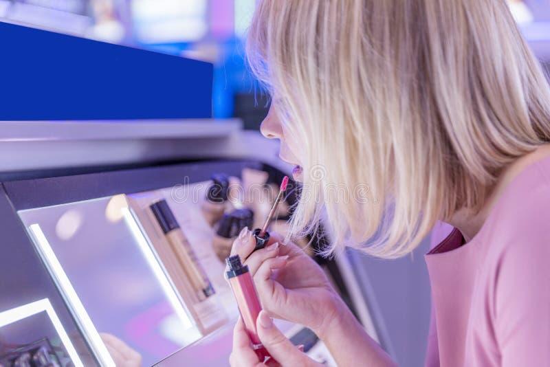Een jonge vrouw in een schoonheidsmiddelenopslag test lippenstift Kijkt in de spiegel en schildert lippen Close-up royalty-vrije stock afbeelding