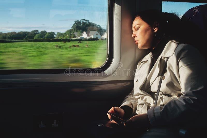 Een jonge vrouw slaapt in een treinvervoer stock foto's