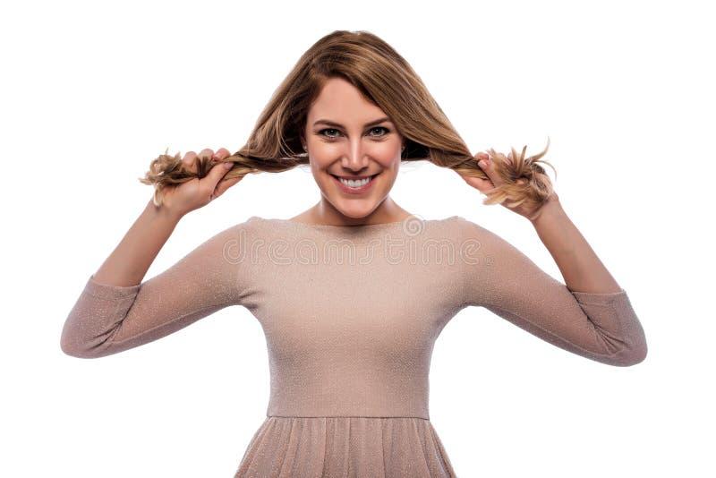 Een jonge vrouw trekt zich bij de vlechten op een witte achtergrond stock afbeeldingen