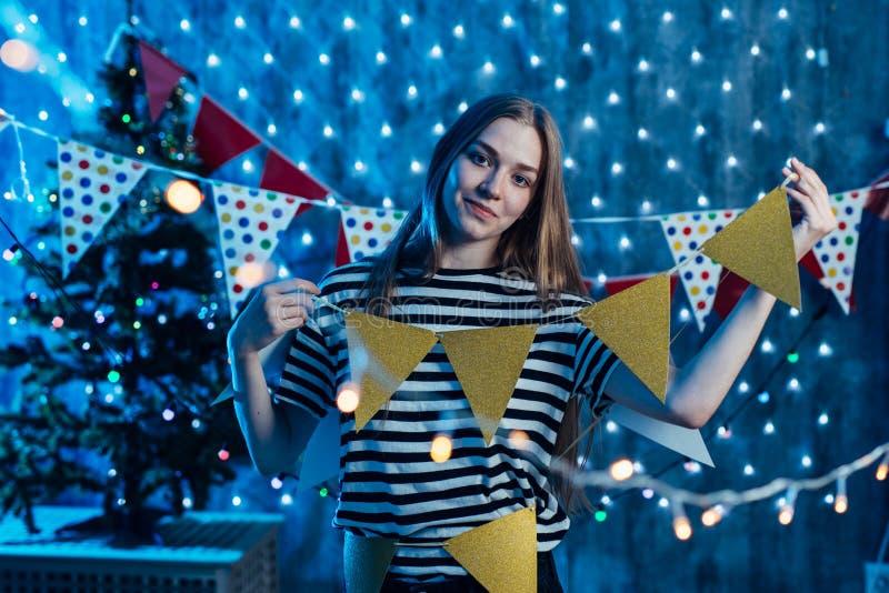 Een jonge vrouw verfraait ruimtevlaggen, slingers die voor vieringskerstmis voorbereidingen treffen stock fotografie