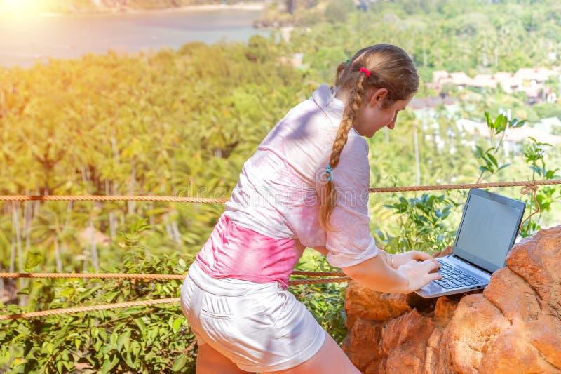 Een jonge vrouw werkt met laptop aan de bovenkant van berg met mening over het zandige tropische strand het werk en het reizen stock foto's