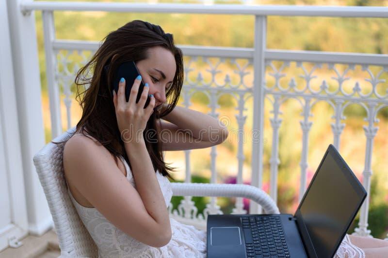 Een jonge vrouw in een witte kleding die bij laptop werken en op een smartphone, het werk op vakantie, het freelance, verre werk  royalty-vrije stock foto