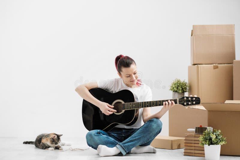 Een jonge vrouw in een witte T-shirt rust en speelt de gitaar op de achtergrond van kartondozen in nieuwe leeg stock foto