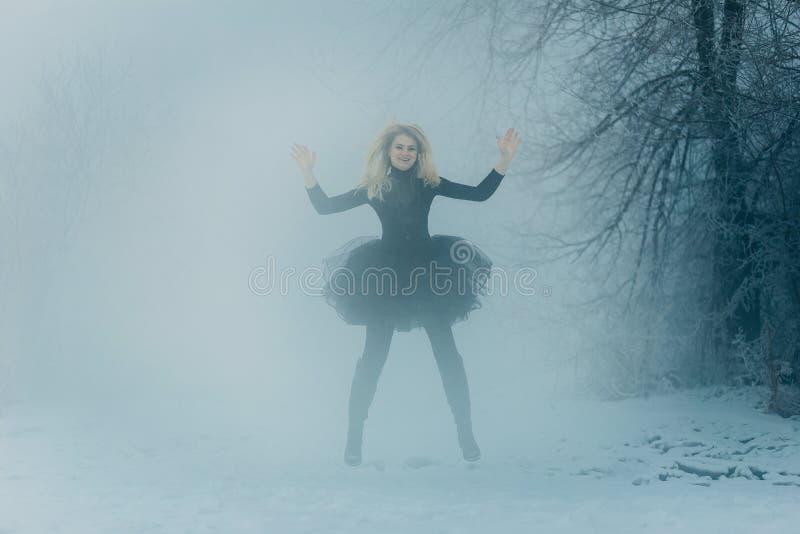 Een jonge vrouw in een zwarte kleding springt de winterbos stock afbeeldingen