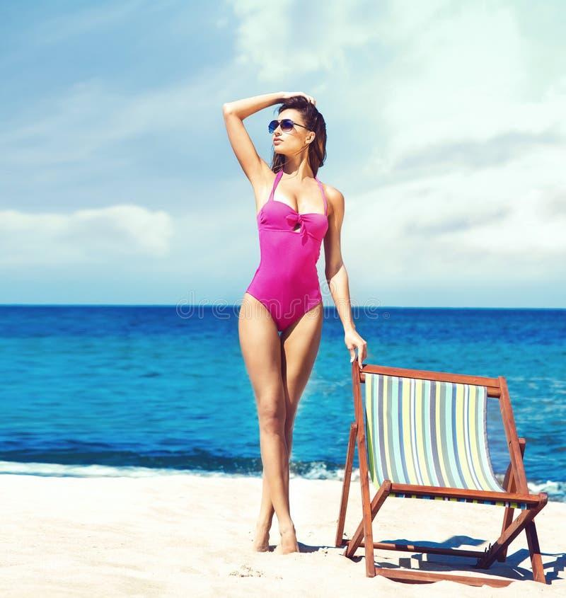 Een jonge vrouw in zwempak het ontspannen op een deckchair op het strand stock fotografie