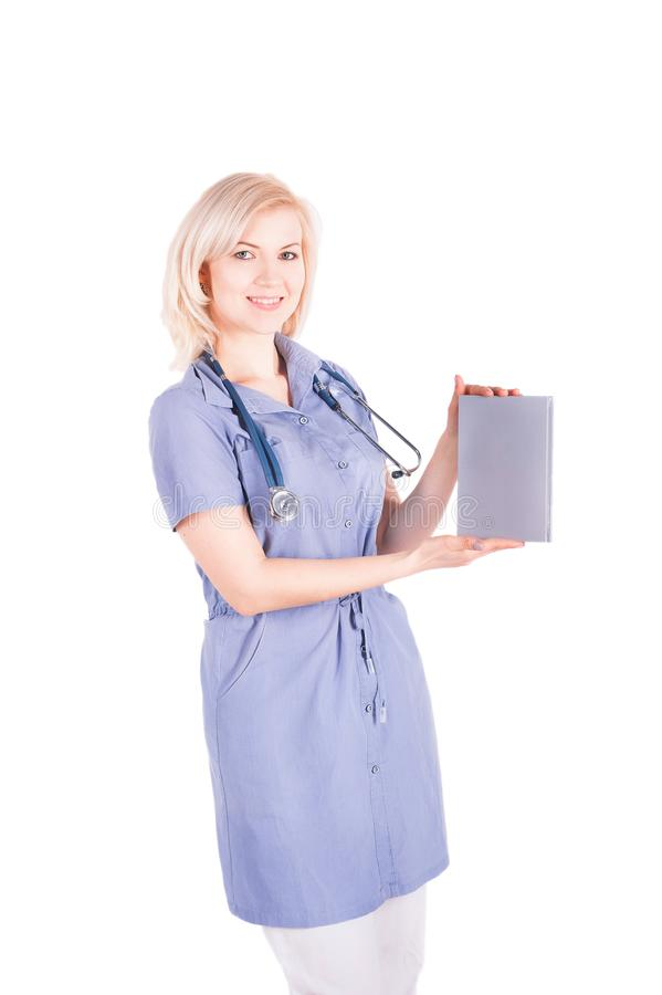 Een jonge vrouwelijke arts in een blauwe robe houdt een grijs grijs notitieboekje op een geïsoleerde witte achtergrond Een blonde stock afbeelding