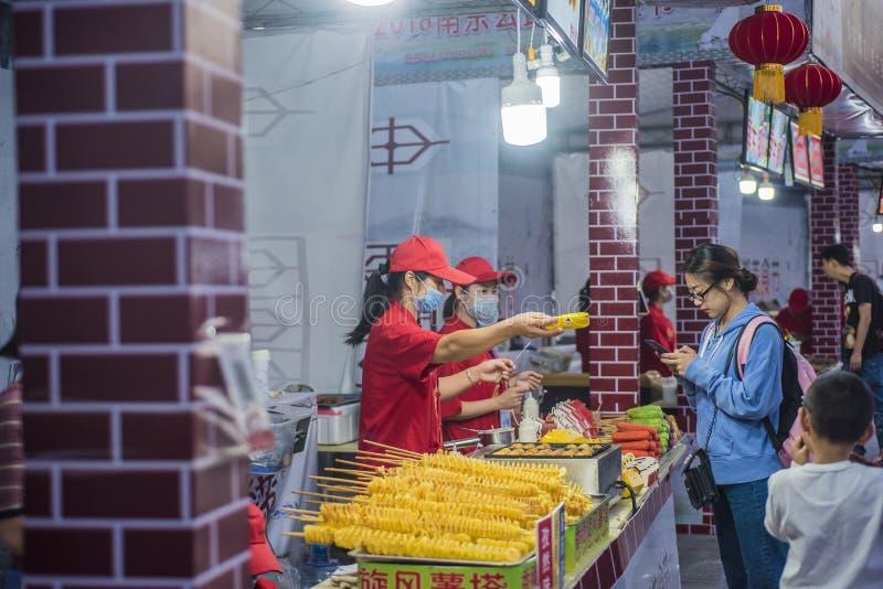 Een jonge vrouwelijke bediende die een rode hoed en een paardestaart met een rood overhemd dragen overhandigt graan aan de klant stock afbeelding