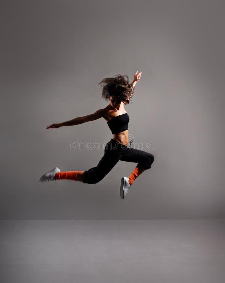 Een jonge vrouwelijke danser voert een sprong uit stock afbeeldingen