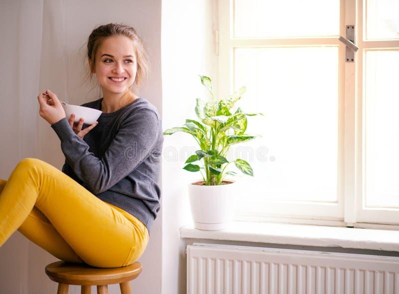 Een jonge vrouwelijke studentenzitting door venster, het eten De ruimte van het exemplaar stock foto