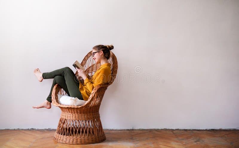 Een jonge vrouwelijke studentenzitting op rieten stoel, lezing De ruimte van het exemplaar stock foto's