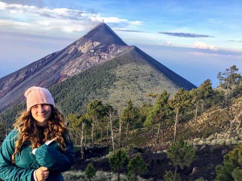 Een jonge vrouwelijke toerist die naast haar kampeerterrein op de vulkaan glimlachen zet Acatenango op royalty-vrije stock afbeeldingen