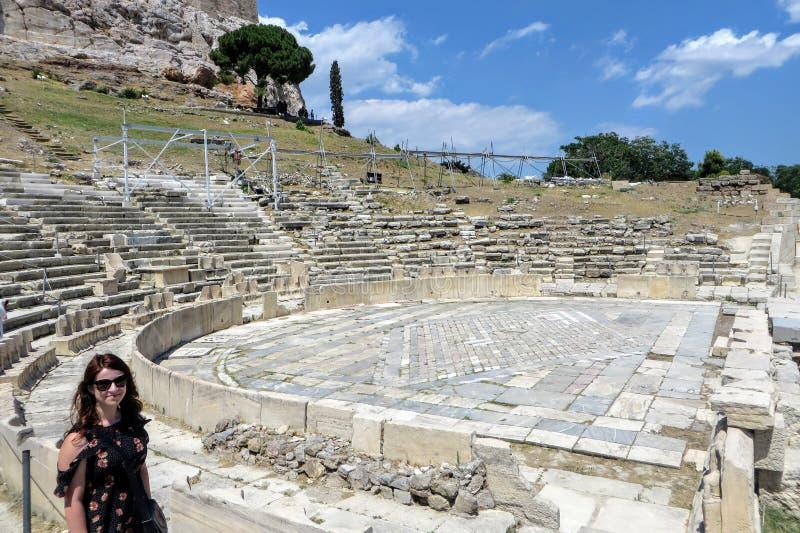 Een jonge vrouwelijke toerist die zich voor het Theater van Dionysus enkel onder de Akropolis in Athene, Griekenland bevinden stock foto's