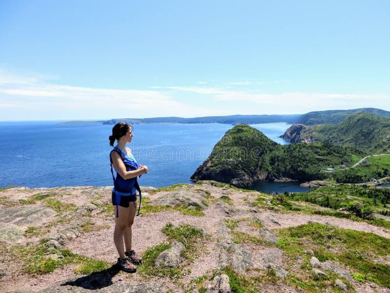Een jonge vrouwelijke wandelaar zich boven de Atlantische Oceaan bevinden die Quidi Vidi overzien en de ruwe kust die van Newfoun stock foto's