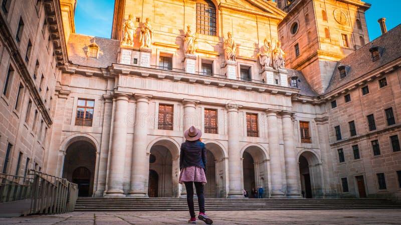Een jonge vrouwentoerist met haar terug voor de Basiliek bij Gr Escorial in Spanje stock foto's