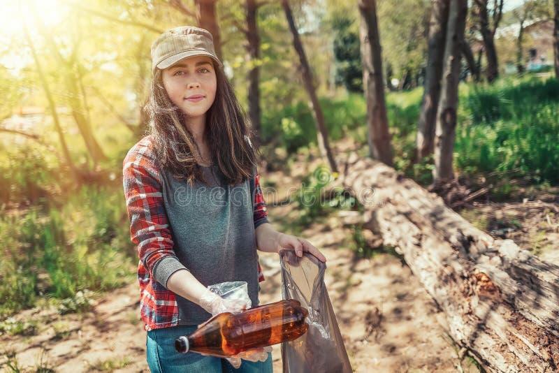 Een jonge vrouwenvrijwilliger verzamelt huisvuil in het Park Het concept aardedag en ecologie en milieubehoud stock afbeeldingen