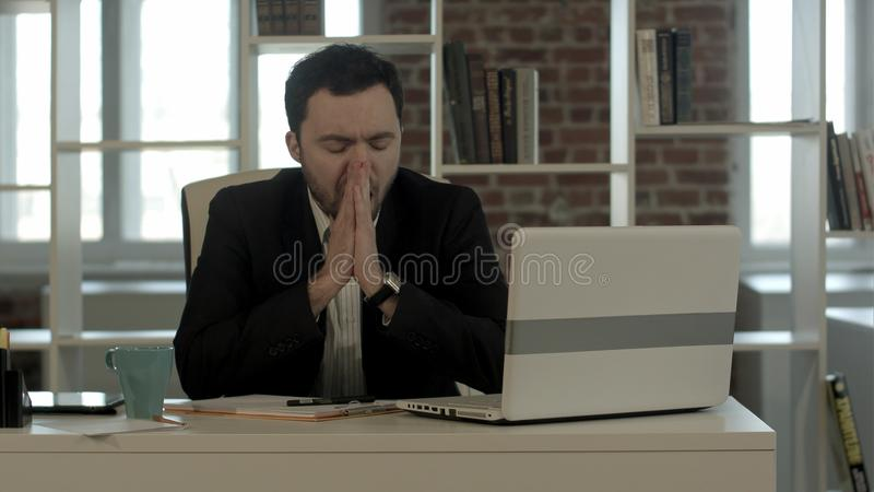Een jonge wanhopige zakenman die in zijn bureau, heeft geen idee en vermoeid neer kijken royalty-vrije stock foto's