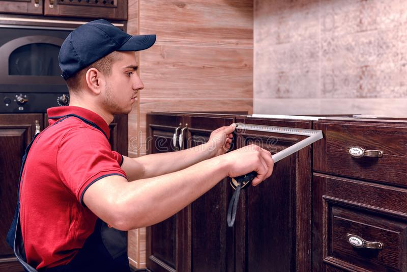 Een jonge werknemer assembleert modern houten keukenmeubilair royalty-vrije stock afbeeldingen