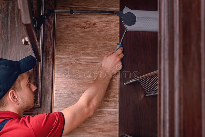 Een jonge werknemer assembleert modern houten keukenmeubilair stock foto