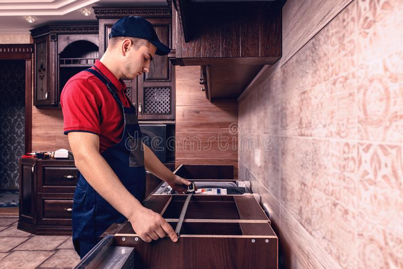Een jonge werknemer assembleert modern houten keukenmeubilair stock afbeeldingen