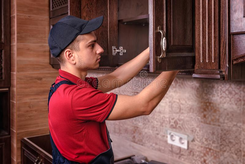 Een jonge werknemer assembleert modern houten keukenmeubilair stock fotografie