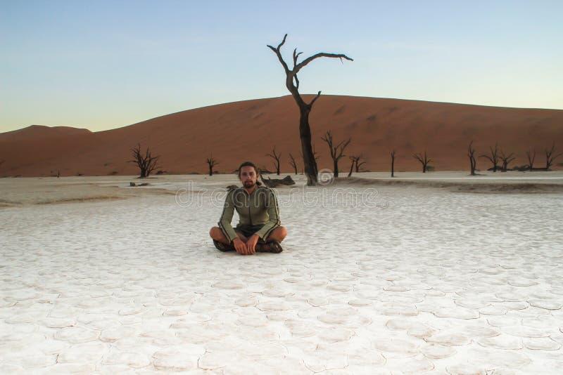 Een jonge witte Kaukasische mannelijke reiziger in sportkledingszitting op een droge witte grond in het Nationale Park van Sousse stock afbeelding