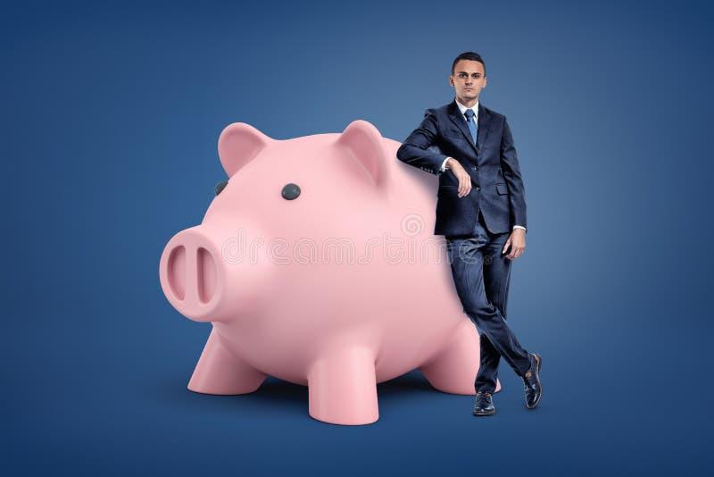 Een jonge zakenman bevindt zich dichtbij een groot roze spaarvarken en leunt op het stock afbeeldingen