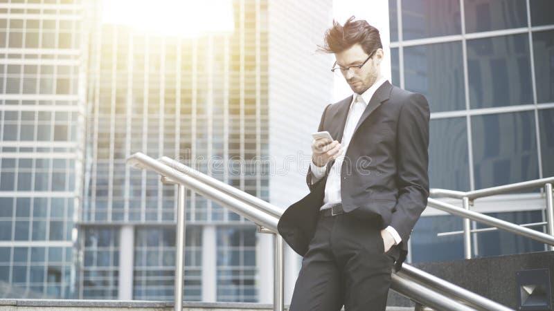 Een jonge zakenman scrolt de telefoon stock afbeeldingen