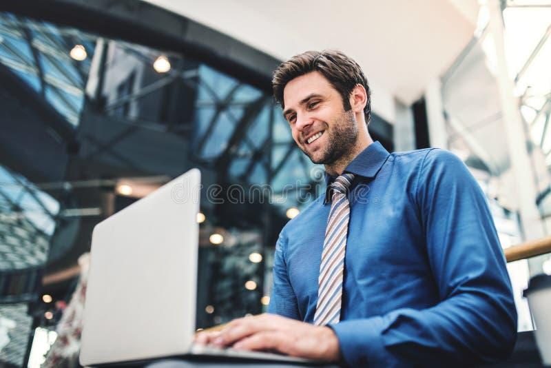 Een jonge zakenmanzitting op een bank in een modern gebouw, die laptop met behulp van stock foto
