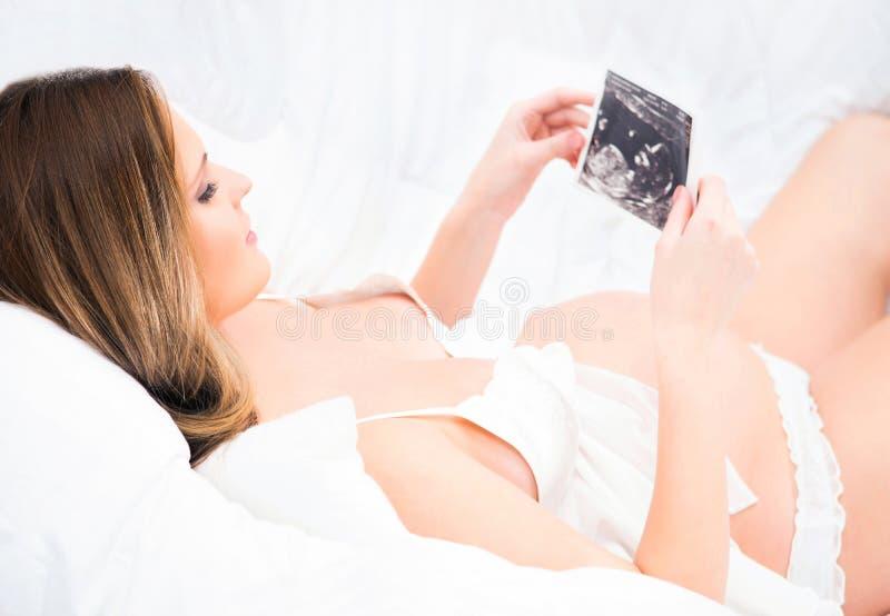 Een jonge zwangere vrouw die in het bed ontspant en ultras houdt stock foto's
