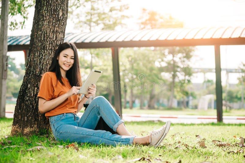 Een jongelui of tiener Aziatische studente op universiteit die en het boek glimlachen lezen en bekijkt de tablet royalty-vrije stock foto